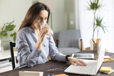 Woman working at home while drinking a glass of ice cold water