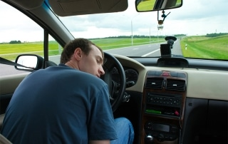 man falling asleep behind the wheel of his car on the side of the road