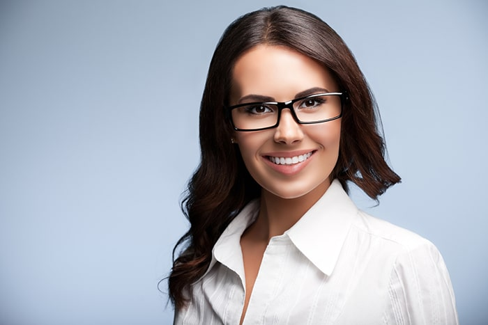 Happy smiling young cheerful brunette businesswoman in glasses, over grey background