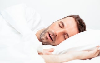 man laying on his side, snoring