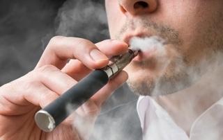 Man is smoking electronic cigarette or vaporizer.