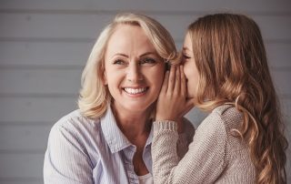 Little girl whispering to her Grandmother. Is it a secret about tooth decay and oral bacteria?