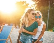 2 young women smiling and laughing on the beach