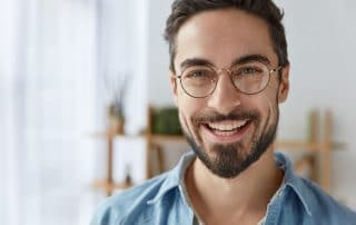 Man with crooked smile and large glasses shows off his mouth. Is it time for a fix?