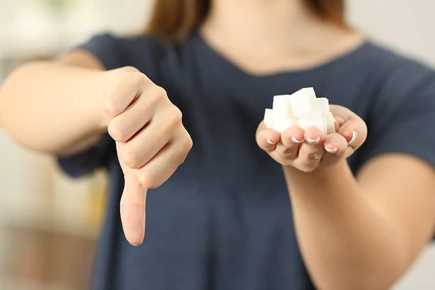 Woman hand holding sugar cubes with thumbs down. Are you ready to cut sugar from your diet?