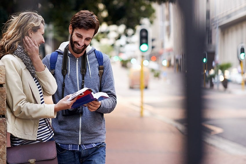Two young individuals walking on the sidewalk looking at a guide, much like our guide to a more whiter smile. As one of the most common cosmetic dental procedures out there, and one of the safest, many patients still don't understand what it is and how it can help them.