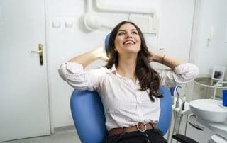 Gorgeous young adult woman enjoying her visit at dentist, relaxed in chair with hands behind her head. With Sedation Dentistry you never have to skip the dentist again.