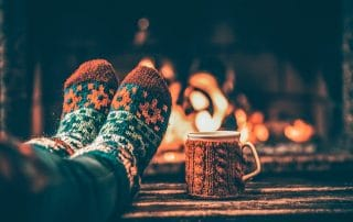 Wool socks of a woman rest on top of a wooden table in front of a warm fire place