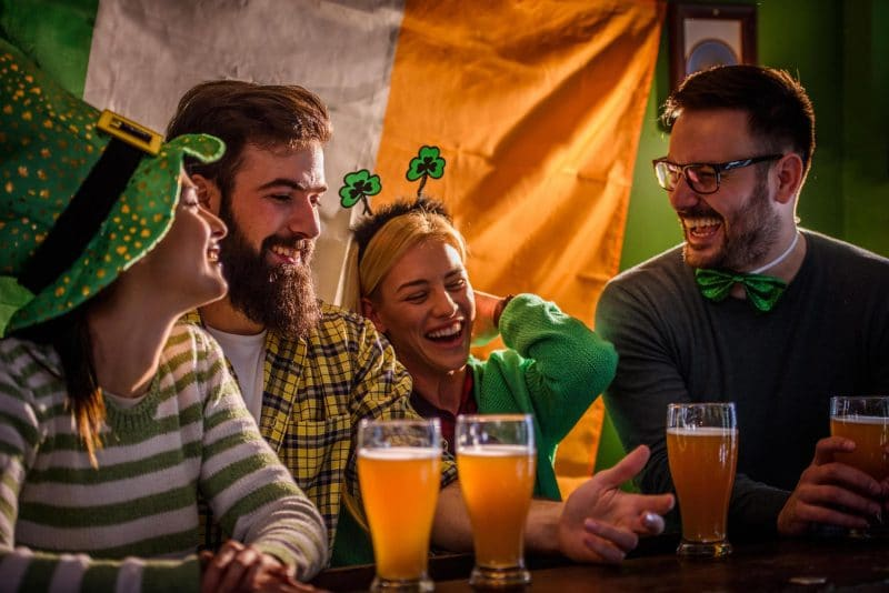 Young people laughing and drinking beer in St Patty's Day gear