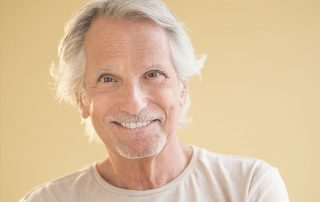 senior man with wavy hair shows off his smile