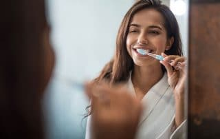 attractive young woman brushing her teeth in front of her bathroom mirror