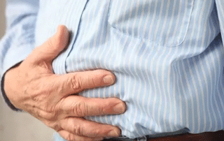 man holding his stomach due to pain
